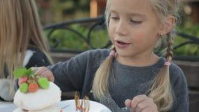 Bambina sveglia che mangia il caffè del dolce all'aperto video d archivio