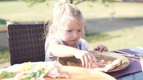 Bambina sveglia che mangia pizza in un caffè sulla via archivi video