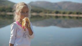 Bambina sveglia che mangia una banana mentre stando video d archivio
