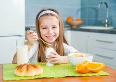 Bambina che mangia la sua prima colazione Fotografia Stock Libera da Diritti