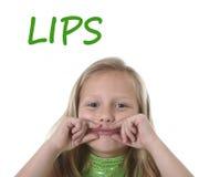 Bambina sveglia che mostra le sue labbra nelle parti del corpo che imparano le parole inglesi alla scuola Fotografia Stock