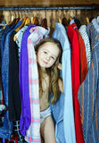 Bambina sveglia che nasconde guardaroba interno dai suoi genitori Fotografia Stock Libera da Diritti