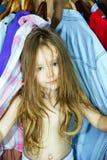 Bambina sveglia che nasconde guardaroba interno dai suoi genitori Immagini Stock