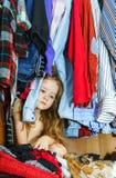Bambina sveglia che nasconde guardaroba interno dai suoi genitori Fotografia Stock