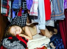 Bambina sveglia che nasconde guardaroba interno dai suoi genitori Immagine Stock Libera da Diritti