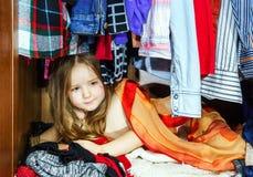 Bambina sveglia che nasconde guardaroba interno dai suoi genitori Fotografie Stock