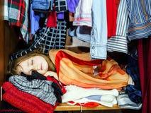 Bambina sveglia che nasconde guardaroba interno dai suoi genitori Immagine Stock