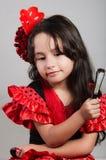 Bambina sveglia che porta bello vestito rosso e nero con la banda capa di corrispondenza, posante per la macchina fotografica fac Fotografie Stock Libere da Diritti