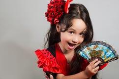 Bambina sveglia che porta bello vestito rosso e nero con la banda capa di corrispondenza, posante per la macchina fotografica fac Immagine Stock