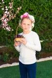 Bambina sveglia che posa con la frutta fresca nel giardino soleggiato Bambina con il canestro dell'uva immagini stock libere da diritti