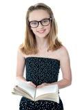 Bambina sveglia che si leva in piedi con un libro aperto Fotografie Stock Libere da Diritti