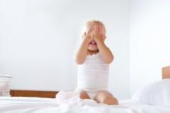 Bambina sveglia che si nasconde con le mani che coprono fronte Fotografie Stock