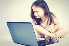 Bambina sveglia che si siede con un computer portatile Immagine Stock