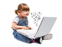 Bambina sveglia che si siede con un computer portatile Fotografie Stock Libere da Diritti