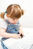 Bambina sveglia che si siede con un computer portatile Immagini Stock Libere da Diritti