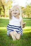 Bambina sveglia che si siede e che ride nell'erba Fotografia Stock