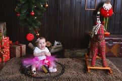 Bambina sveglia che si siede sotto l'albero di Natale Bambino che gioca con un treno del giocattolo Immagine Stock
