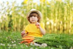 Bambina sveglia che si siede su un'erba verde che mangia carota Immagine Stock Libera da Diritti