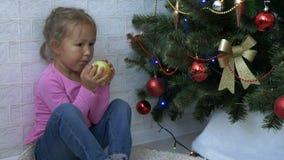 Bambina sveglia che si siede sul pavimento e che mangia mela accanto ad un albero di Natale video d archivio