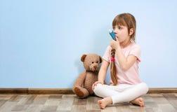 Bambina sveglia che si siede sul pavimento mentre per mezzo dell'inalatore Immagine Stock Libera da Diritti