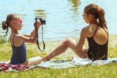 Bambina sveglia che si siede sull'erba il giorno di estate soleggiato e che prende immagine con la macchina fotografica Vacanze e fotografia stock libera da diritti