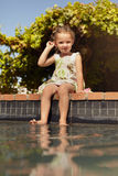 Bambina sveglia che si siede sull'orlo di una piscina Fotografia Stock