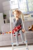 Bambina sveglia che si siede sulla scaletta nel paese Immagine Stock