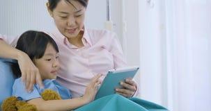 Bambina sveglia che si trova sul letto con sua madre in ospedale, fumetti divertenti di sorveglianza sulla compressa digitale archivi video