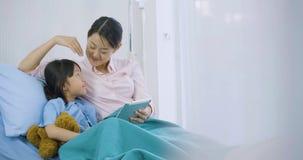 Bambina sveglia che si trova sul letto con sua madre in ospedale, fumetti divertenti di sorveglianza sulla compressa digitale video d archivio
