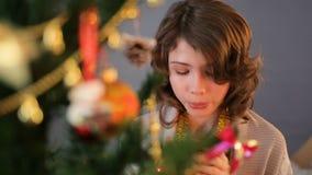 Bambina sveglia che soffia in tazza di cioccolata calda, bambino che sta l'albero di abete vicino video d archivio