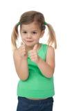 Bambina sveglia che sorride alla macchina fotografica che dà i pollici su Fotografie Stock Libere da Diritti