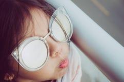 Bambina sveglia che sorride con gli occhiali da sole fotografie stock libere da diritti