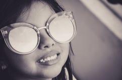 Bambina sveglia che sorride con gli occhiali da sole fotografia stock libera da diritti