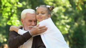 Bambina sveglia che sorride e che abbraccia suo nonno, tempo libero con la famiglia video d archivio