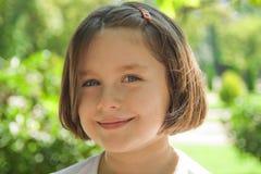 Bambina sveglia che sorride in giorno pieno di sole Immagini Stock Libere da Diritti