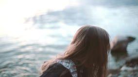 Bambina sveglia che sta sulla riva vicino all'acqua ed ai tiri una pietra nell'acqua video d archivio