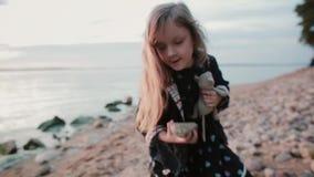 Bambina sveglia che sta sulla riva vicino all'acqua La femmina getta una grande pietra nel lago sul tramonto video d archivio