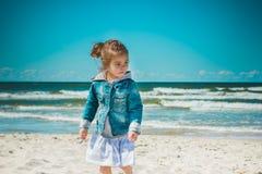 Bambina sveglia che sta sulla spiaggia Immagine Stock