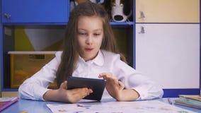 Bambina sveglia che studia alla biblioteca che fa compito con il PC della compressa Scuola elementare Lettura del bambino archivi video