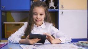 Bambina sveglia che studia alla biblioteca che fa compito con il PC della compressa Scuola elementare Lettura del bambino stock footage