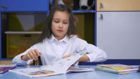 Bambina sveglia che studia alla biblioteca che fa compito e sorridere Scuola elementare Lettura del bambino stock footage