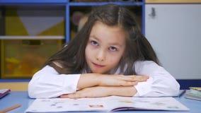 Bambina sveglia che studia alla biblioteca che fa compito e sorridere Scuola elementare Lettura del bambino video d archivio