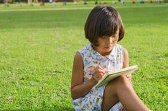 Bambina sveglia che studia alla scuola Immagine Stock