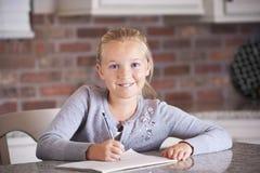 Bambina sveglia che studia e che scrive Immagini Stock