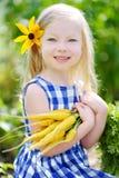 Bambina sveglia che tiene un mazzo di carote gialle fresche Immagine Stock Libera da Diritti