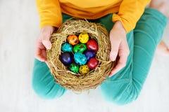 Bambina sveglia che tiene un nido con le uova di Pasqua colorate a casa sul giorno di Pasqua Fotografia Stock Libera da Diritti