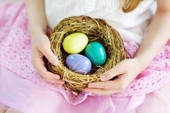 Bambina sveglia che tiene un nido con le uova di Pasqua colorate a casa sul giorno di Pasqua Fotografie Stock Libere da Diritti