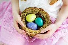 Bambina sveglia che tiene un nido con le uova di Pasqua colorate a casa sul giorno di Pasqua Immagini Stock