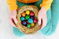 Bambina sveglia che tiene un nido con le uova di Pasqua colorate a casa sul giorno di Pasqua Celebrazione della Pasqua alla molla Immagine Stock