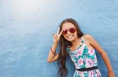 Bambina sveglia con gli occhiali da sole che gesturing il segno di pace Fotografie Stock